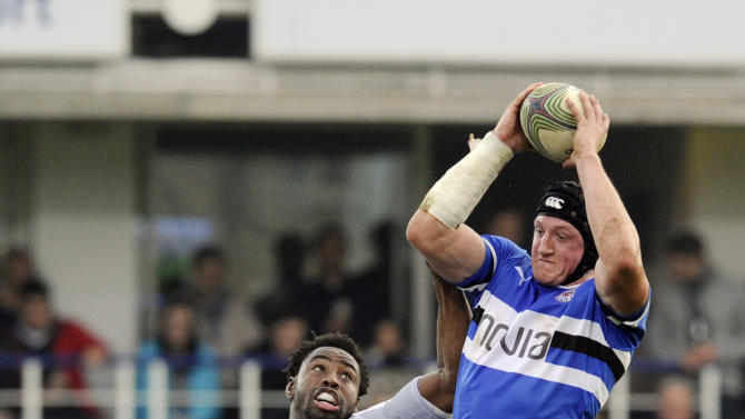 CORRECTS IDENTITY Bath's Stuart Hooper, top right, wins the lineout ball from Montpellier's Fulgence Ouedraogo during their Heineken Cup pool 3 rugby match at the Recreation ground, Bath, England, Sunday, Nov. 20, 2011. (AP Photo/Tom Hevezi)