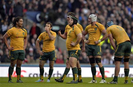 Australian team members react after being defeated by England in their international rugby union test match in London