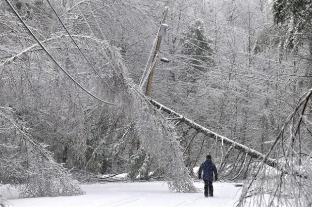 Karen Gibbs walks through a labyrinth of icy broken trees and downed power lines to her home on Maplehurst Drive in Belgrade, Maine on Thursday, Dec. 26, 2013. Southeast Maine and parts of the state's interior that have been without electricity since Sunday anticipated 3 to 7 inches of snow by the time the latest system pushed off the coast Thursday night. Utilities worried that the additional weight on branches and transmission lines could cause setbacks in the around-the-clock efforts to restore power. (AP Photo/The Central Maine Morning Sentinel, Michael G. Seamans)