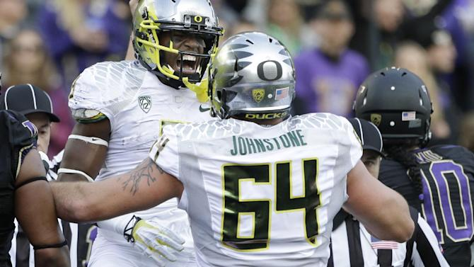 Oregon running back Byron Marshall, left, celebrates his touchdown against Washington with Tyler Johnstone (64) in the first half of an NCAA college football game, Saturday, Oct. 12, 2013, in Seattle