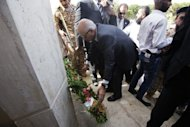 Mohammed al-Megaryef (C), president of Libya's General National Congress, lays a wreath at the US Ambassador's residence in Benghazi, Libya
