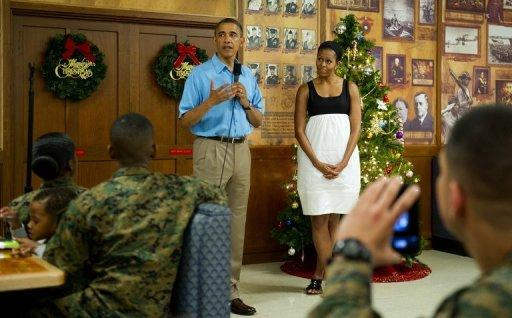 """US President Barack Obama and First Lady Michelle Obama talk with members of the military and their families at Marine Corps Base Hawaii in Kaneohe Bay, Hawaii, December 25, 2012. Obama returns on Thursday to a sharply divided Washington under pressure to forge a year-end deal with Republicans to avoid the tax hikes and spending cuts of the """"fiscal cliff."""""""