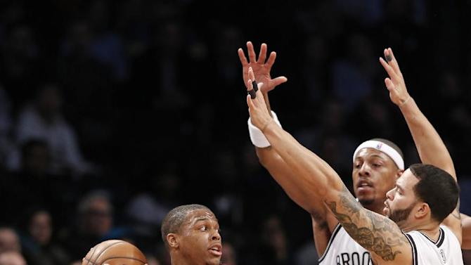 Brooklyn Nets forward Paul Pierce (34) and Nets guard Deron Williams (8) defend Toronto Raptors guard Kyle Lowry, left, in the first half of an NBA basketball game, Monday, Jan. 27, 2014, in New York