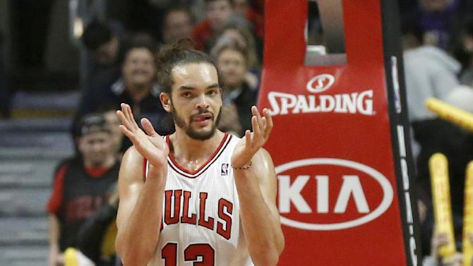 Chicago Bulls center Joakim Noah applauds his teammates during the second half of an NBA basketball game against the Boston Celtics, Thursday, Jan. 2, 2014, in Chicago. The Bulls won 94-82