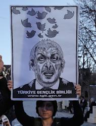 A member of the Turkish Youth Union holds up a cartoon depicting Turkey's Prime Minister Recep Tayyip Erdogan during a protest against a ban on Twitter, in Ankara, Turkey, Friday, March 21, 2014. Turkey's attempt to block access to Twitter appeared to backfire on Friday with many tech-savvy users circumventing the ban and suspicions growing that the prime minister was using court orders to suppress corruption allegations against him and his government. (AP Photo/Burhan Ozbilici)