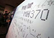 Family members of passengers onboard the missing Malaysian Airlines flight MH370 write messages to their missing relative on a board at a hotel in Beijing March 20, 2014. REUTERS/Kim Kyung-Hoon