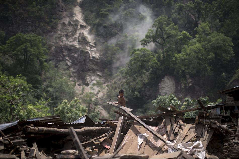 A boy clears rubble from his home during a landslide after Tuesday's earthquake at Singati Village, in Dolakha, Nepal