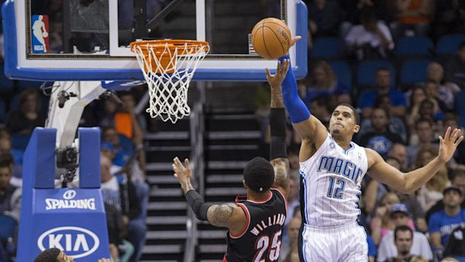 Orlando Magic's Tobias Harris (12) attempts to block Portland Trail Blazers Mio Williams shot while Ronnie Price (10) watches during the first half of an NBA basketball game in Orlando, Fla., Tuesday, March 25, 2014
