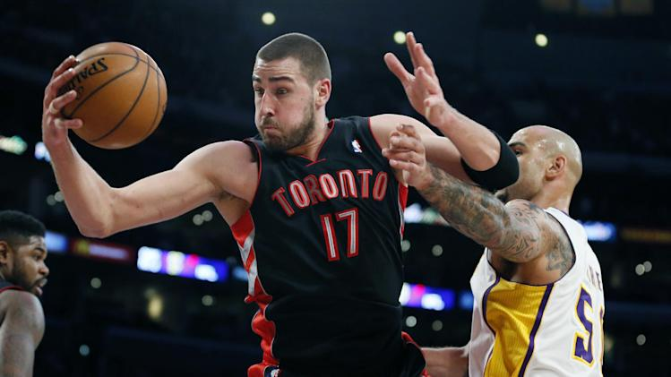 Toronto Raptors' Jonas Valanciunas, left, of Lithuania, brings in a defensive rebound in front of Los Angeles Lakers' Robert Sacre, right, during the first half of an NBA basketball game in Los Angeles, Sunday, Dec. 8, 2013
