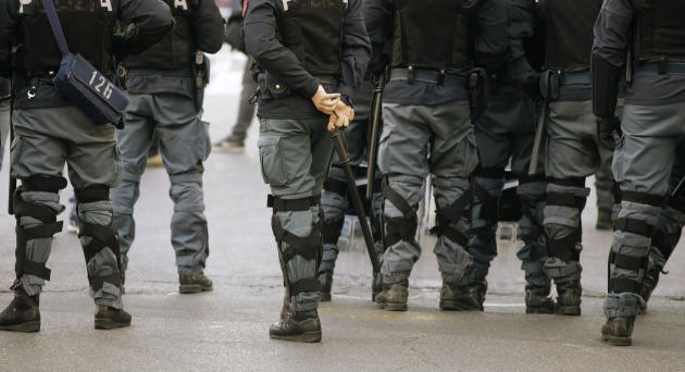 Italian policemen in riot gear walk ahead demonstrators during a counter-demonstration against Italian Northern League protesters poured simultaneously in Rome and against Italian government, Saturday