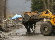 Workers dig through debris using heavy equipment in the mudslide near Oso, Washington March 25, 2014. REUTERS/Ted S. Warren/Pool