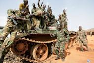 Sudanese soldiers pose on a seized tank in the oil region of Heglig in April 2012. Sudan's army on Wednesday said it had fought with South Sudanese troops and their rebel allies, expelling them from two areas along the border