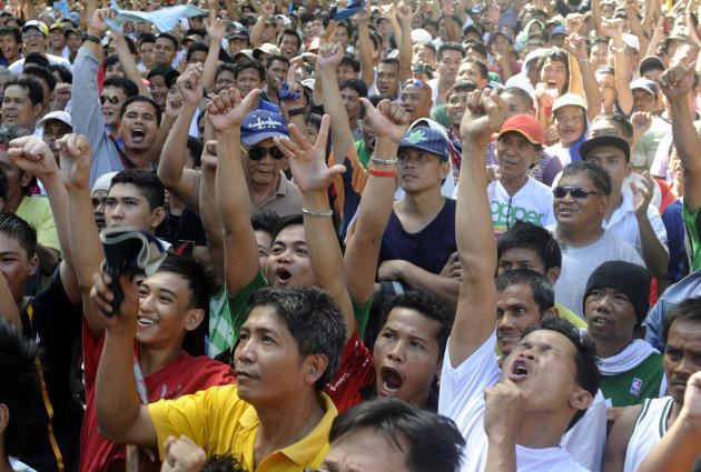 Thousands of people celebrate in a public square as national boxing hero Manny Pacquiao is announced the winner of his bout against Mexican Juan Manuel Marquez, in Manila on November 13, 2011. 32-year-old Pacquiao retained his World Boxing Organisation welter weight title but only after a hard fight which initially left some Filipinos fearful their hero might lose for the first time since 2005. AFP PHOTO / JAY DIRECTO (Photo credit should read JAY DIRECTO/AFP/Getty Images)