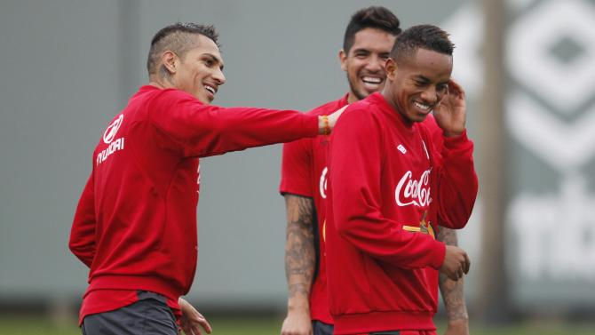 Peru's national soccer player Paolo Guerrero jokes with Andre Carrillo near Juan Vargas during a training session in Lima