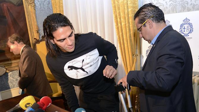 Colombian soccer star Radamel Falcao is helped with his crutches by Doctor Carlos Ulloa, right, also from Colombia after a press conference at the Trindade Hospital in Porto, Portugal, Monday, Jan. 27, 2014. Colombia and Monaco's striker Falcao is in a race against time to get fit for the World Cup in June after undergoing knee surgery Saturday, Jan. 25, with his doctor giving him a better than 50-50 chance of making it