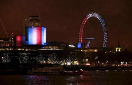 Following the attacks in Paris, the blue, white and red colours of France's national flag are projected onto the National Theatre and the London Eye in London, Britain November 14, 2015. REUTERS/Suzanne Plunkett