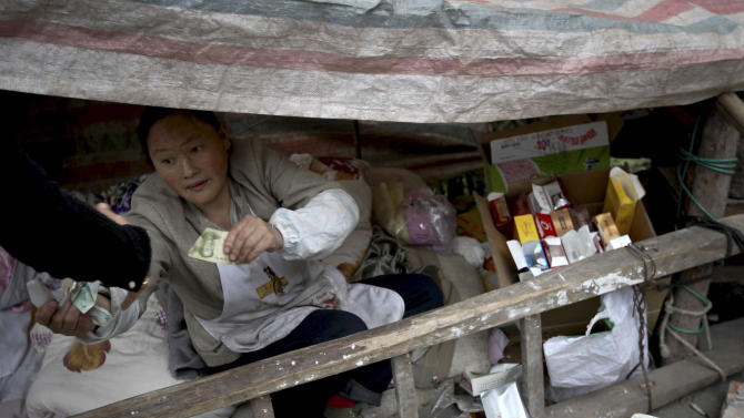 A woman opens business in a shelter near  her damaged shop after the earthquake in Yuxi village of Baosheng township in Lushan county in southwest China's Sichuan province Sunday, April 21, 2013. Saturday's earthquake in Sichuan province killed over 200 people, China's Xinhua News Agency said. (AP Photo) CHINA OUT
