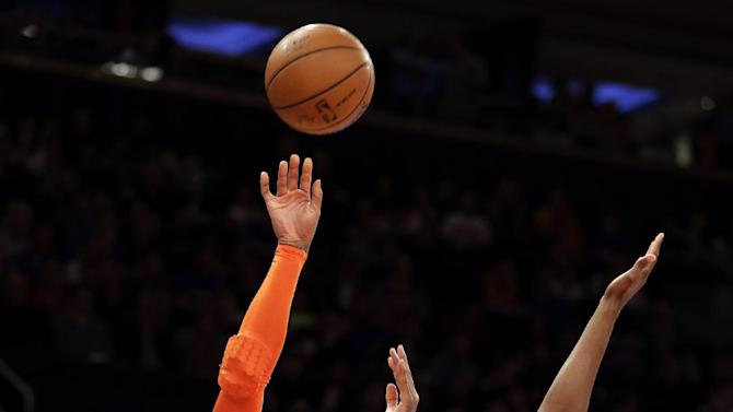 New York Knicks' Carmelo Anthony, left, shoots the ball against Milwaukee Bucks' Khris Middleton in the first quarter of an NBA basketball game at New York's Madison Square Garden, Saturday, March 15, 2014