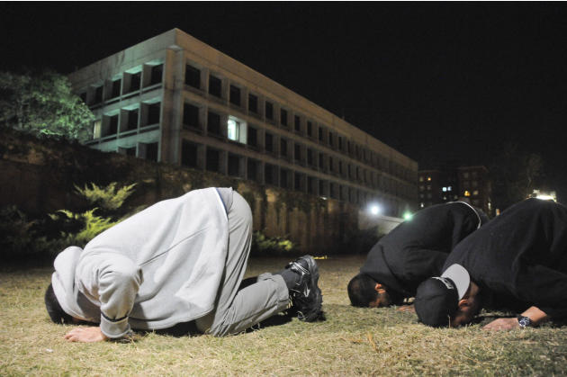 Three freed Guantanamo Bay detainees, who were resettled in Uruguay, pray during their protest outside the U.S. embassy in Montevideo, Uruguay, Friday, April 24, 2015. From left to right Omar Abdelahd