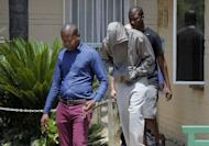 South African Olympic sprinter Oscar Pistorius (C) leaves the Boshkop police station in Pretoria East on February 14, 2013. South African police said Thursday they have charged Pistorius with the Valentine's Day murder of his model girlfriend, playing down reports she was mistaken for a burglar