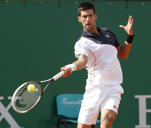 Novak Djokovic of Serbia returns the ball to Pablo Carreno Busta of Spain during their third round match of the Monte Carlo Tennis Masters tournament in Monaco, Thursday, April 17, 2014. Djokovic won