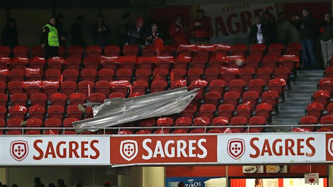 People look at a sheet of aluminum that fell on the stands after people started leaving their seats before the start of the Portuguese league soccer match between Benfica and Sporting Sunday, Feb. 9 2014, at Benfica's Luz stadium in Lisbon. Strong winds damaged the stadium roof before kick off and debris fell on the pitch and stands. It was decided the match should be postponed for safety reasons