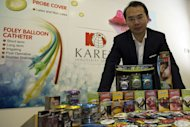 Karex executive director Goh Miah Kiat poses for pictures with his company's condom production in the Malaysian town of Pontian, on January 22, 2013. Karex already claims to be the world's biggest condom maker by volume, but is planning an IPO to fund a doubling of output