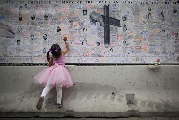 A girl reaches to touch a wall of remembrances set up on the ground zero fence in New York, Saturday, Sept. 10, 2011. (AP Photo/Oded Balilty)