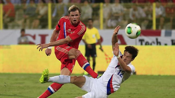 Russia's midfielder Dmitry Tarasov, left, shoots the ball as South Korea's Jongwoo Park, tries to block him during the international friendly soccer match between Russia and South Korea, in Dubai, United Arab Emirates, Tuesday, Nov. 19, 2013