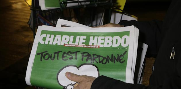 FILE - In this Wednesday, Jan. 14, 2015, file photo, a seller of newspapers stocks several Charlie Hebdo newspapers at a newsstand in Nice, France. Under armed security and a cloud of conflicted opinions and emotions, the French satirical magazine Charlie Hebdo was presented a freedom of expression award on Tuesday, May 5, 2015, in New York, from the PEN American Center. In accepting the award, Editor-in-Chief Gerard Biard noted the magazine's history of shocking readers with its irreverent drawings of religious figures. (AP Photo/ Lionel Cironneau, File)
