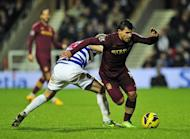 Manchester City's Argentinian striker Sergio Aguero (R) vies with Queens Park Rangers' English midfielder Shaun Derry (L) during the English Premier League football match between Queens Park Rangers and Manchester City at Loftus Road in London, England on January 29, 2013. The game finished 0-0