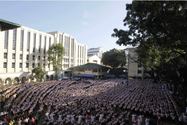 Thousands of students and faculty members dance to the theme song of the One Billion Rising campaign in the quadrangle of the St. Scholastica college in Manila