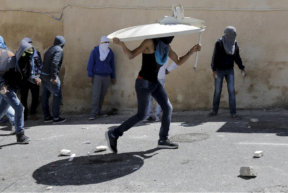 A Palestinian youth uses a satellite dish as shield during clashes in the East Jerusalem neighbourhood of A-tur