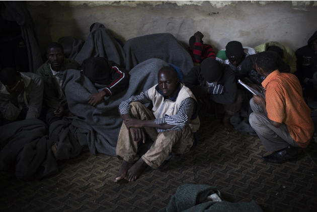 FILE - In this file photo taken Friday, Nov. 29, 2013, African migrants cover themselves with blankets, after being captured by the Libyan Coast Guard while on a boat heading to Italy, in a detention
