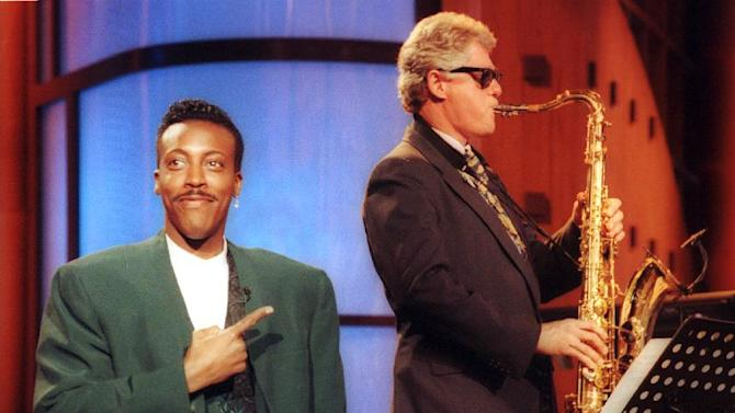 """FILE - This June 3, 1992 file photo shows Arkansas Gov. Bill Clinton, right, playing the saxaphone with the band during the musical opening of """"The Arsenio Hall Show, """" in the Hollywood section of Los Angeles.  The role of female talk-show hosts in late-night TV network history, all 50-plus years of it, can be summed up in two words: Joan Rivers. It takes just another two _ Arsenio Hall _ to do the same for minorities. There's no indication that's going to change in the latest round of musical chairs involving """"Tonight"""" and """"Late Night."""" (AP Photo/Reed Saxon, file)"""