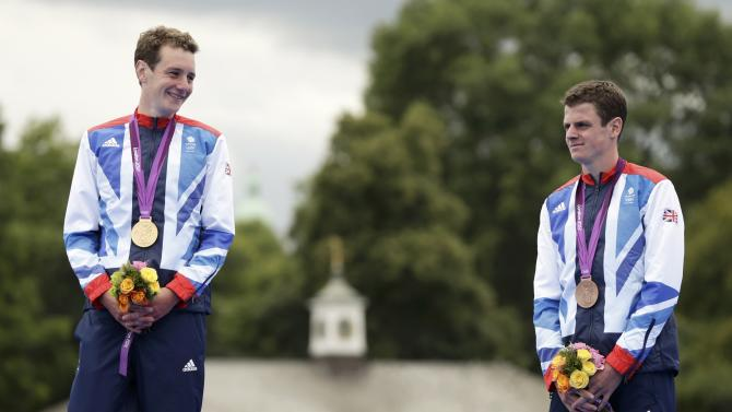 Britain's Alistair Brownlee celebrates his gold medal with his brother Jonathan Brownlee who placed third after the men's triathlon final during the London 2012 Olympic Games at Hyde Park