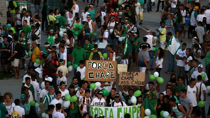 """Fans holding signs that reads: """"Force Chape"""" gather around the Maracana stadium during a symbolic event to remember the Chapecoense soccer team in Rio de Janeiro"""