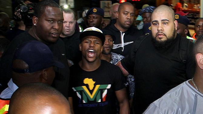 "Boxer Floyd Mayweather Jr, center, on his arrival in Johannesburg Wednesday Jan 15, 2014. Mayweather Jr. is in the country for a six-day visit that the government hopes will help ""resuscitate"" boxing in the country. (AP Photo)"