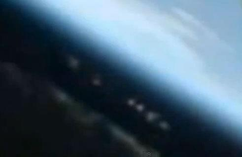 Is this an elongated UFO and accompanying fleet hovering above Earth, or a reflection?