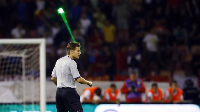A fan uses a laser pointer on referee Brych during the 2014 World Cup qualifying soccer match between Serbia and Croatia in Belgrade