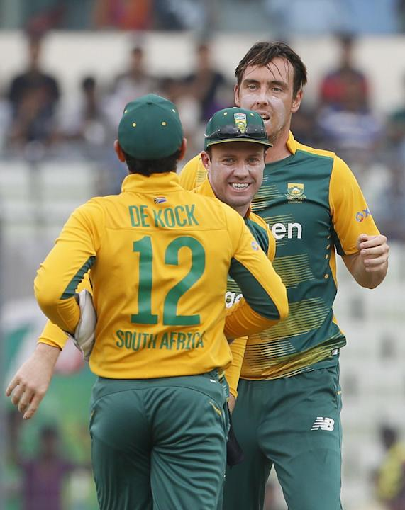 South Africa's Kyle Abbott, celebrates with his teammates AB de Villiers, center, and Quinton de Kock back to camera after the dismissal of Bangladesh's Tamim Iqbal,   during their first Twenty20 inte