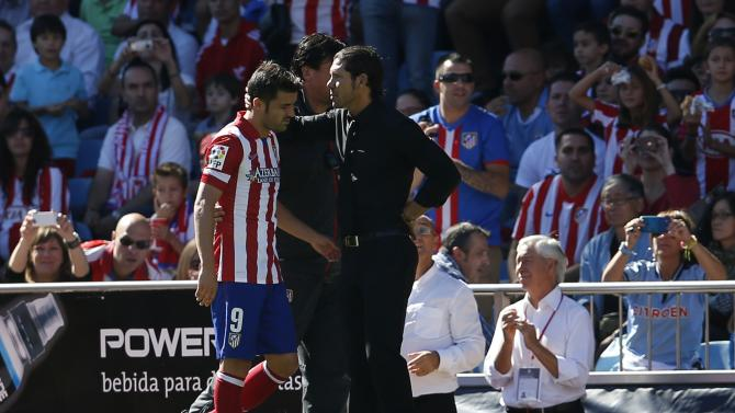 Atletico Madrid's Villa is comforted by coach Simeone after getting substituted during their Spanish first division soccer match against Celta Vigo in Madrid