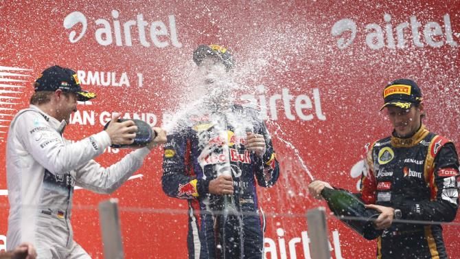 Mercedes Formula One driver Rosberg and Lotus F1 Formula One driver Grosjean spray champagne on the face of Red Bull Formula One driver Vettel on the podium after the Indian F1 Grand Prix at the Buddh International Circuit in Greater Noida