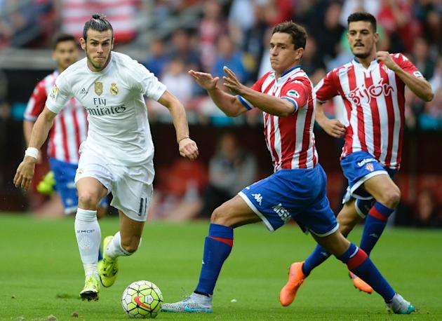 Real Madrid's Gareth Bale (L) fights for the ball with Sporting Gijon's Bernardo during their Spanish La Liga match, at the El Molinon stadium in Gijon, on August 23, 2015