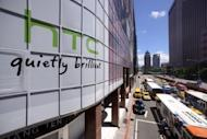 The HTC logo is displayed on a billboard above a busy street in Taipei. The leading smartphone maker said Sunday it has reached a global settlement with Apple, bringing an end to all outstanding litigation between the two companies