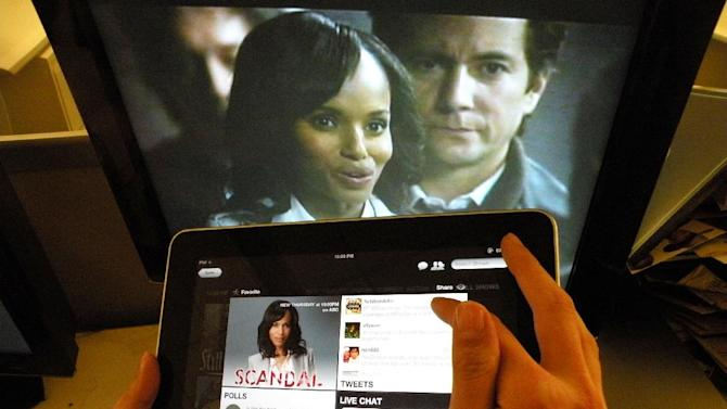 """Kerry Washington from the ABC's """"Scandal,"""" is shown on a TV monitor as an iPad displays the show page on the Yap.tv social media website in New York, Wednesday, May 2, 2012. TV viewing is increasingly expanding to a second screen_whether smartphone or tablet. (AP Photo/Frazier Moore)"""
