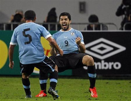 Uruguay's Suarez celebrates with team-mate Gargano after scoring his second goal against Peru during their 2014 World Cup qualifying soccer match in Lima