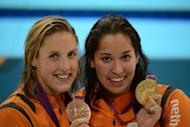 Netherlands' Ranomi Kromowidjojo (R) poses on the podium with the gold medal flanked by silver medalist Netherlands' Marleen Veldhuis after winning the women's 50m freestyle final during the swimming event at the London 2012 Olympic Games