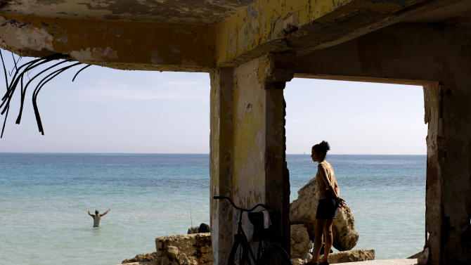 In this May 23, 2013 photo, a woman stands in what remains of a destroyed school as she watches a fisherman on the shores of Havana, Cuba. With its coastal towns and cities, the Caribbean is one of the most vulnerable regions to a changing climate. Hundreds of villages are threatened by rising seas, and more frequent and stronger hurricanes have devastated agriculture in Haiti and elsewhere. (AP Photo/Franklin Reyes)