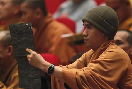 A Buddhist monk films, with an iPad, the closing ceremony of the seventh congress of Vietnam's Buddhist Sangha Association in Hanoi